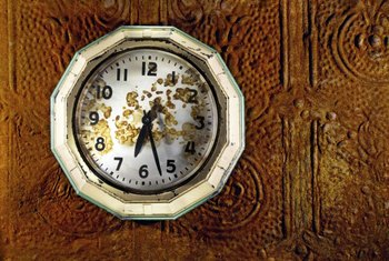 Faux-rust coated tin tile is a backdrop for a folk art clock.