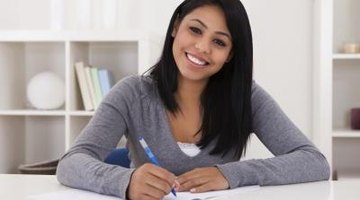 Student smiling while writing in notebook at home