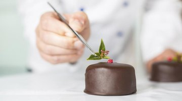 A pastry chef places a garnish on a chocolate tart