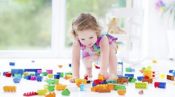 Kindergartner playing with assortment of colored blocks.