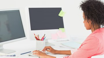 Web designer sitting in front of two desktops