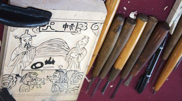 A carved woodblock and set of cutting tools.