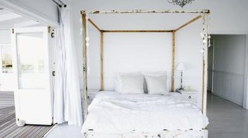 Four poster bed enclosed with white material.