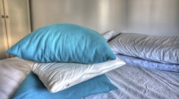 A stack of blue and white pillows on the bed.