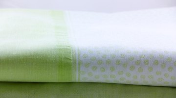A folded light green and white bed sheet.