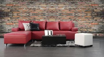 Red leather couch with contrasting block tables and throw pillows.