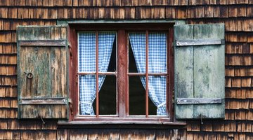 A cottage window with blue gingham curtains.