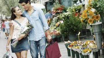 A young couple walks together with shopping bags and flowers.
