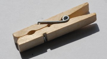 Any spring-loaded clothespin will keep the pennies separated until you squeeze them together.