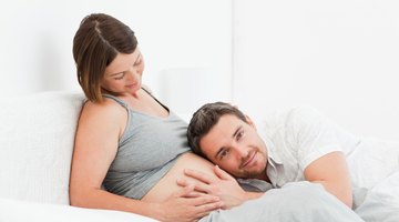 Three women sitting on sofa, two feeling pregnant woman's bump