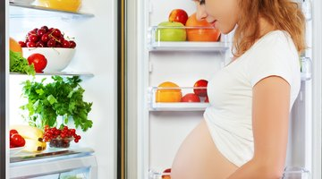 Pregnant woman prepares vegetable salad at home