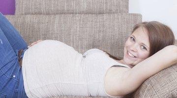 Pregnant Asian woman reclining on sofa