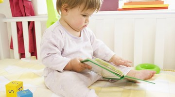 Adorable toddler girl reading book sitting on white bed