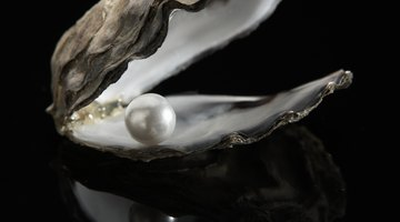 Cultured pearl on black background defines iridescent finish.