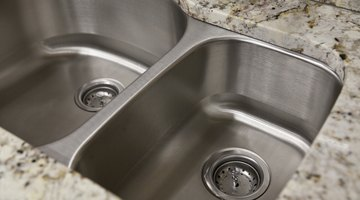 A close-up of two stainless steel sinks in a granite countertop.