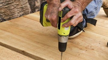 A construction worker is using a cordless drill.