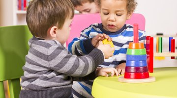 Toddlers coloring and playing with blocks at daycare
