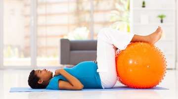 Woman doing downward dog yoga pose with her son in living room
