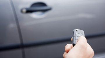 Hand holding remote car entry remote near car door handle