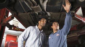 Hands of mechanic working under car