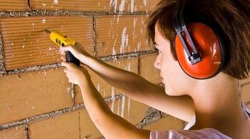 Woman drills into brick wall