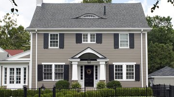 A light gray home with a dark gray door and shutters.