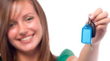 Teenage girl (15-17) holding car keys, smiling, close-up, portrait