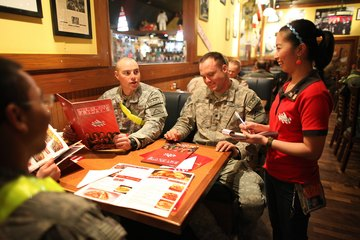 A waitress at a T.G.I.F. takes the orders of servicemen.