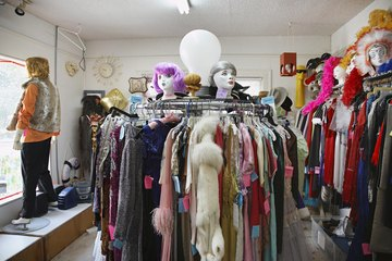 Vintage clothing hangs on racks in a second hand store.