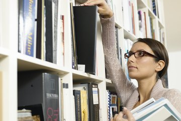 A librarian assistant removes books from a shelf.