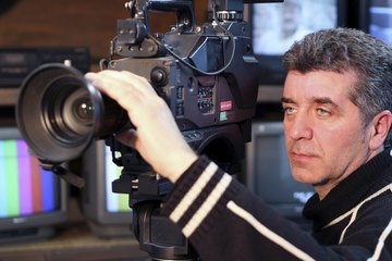 A movie producer holding a professional video camera.