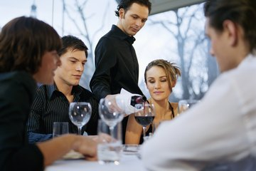 A server pours wine at a table.