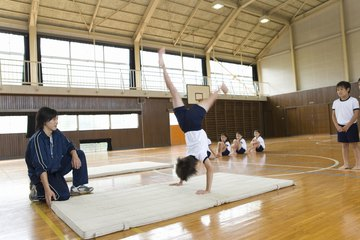 PE teacher working with students in gym on gymnastics mat