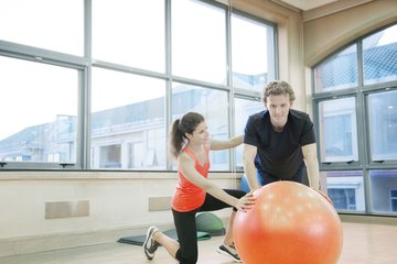 Physical trainer working with man on exercise ball