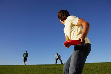 People playing Frisbee on a grassy field.