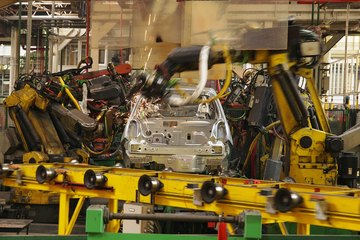Image of a car on an assembly line being welded.