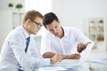 Image of two businessmen having a meeting and working over a laptop.