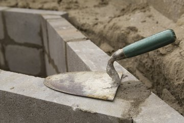 A trowel resting on a brick wall under construction