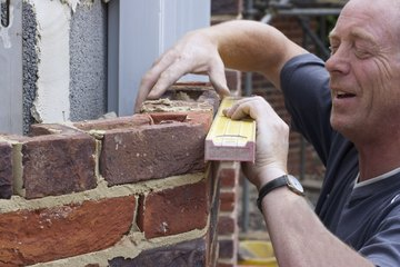 Bricklayer inspecting newly constructed wall