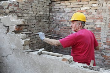 Man using a jointer on a old brick wall
