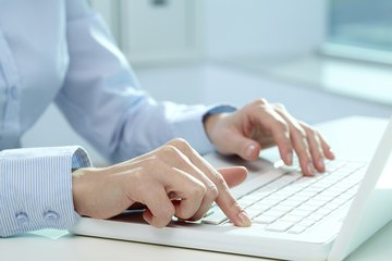 Close-up of hands typing on computer