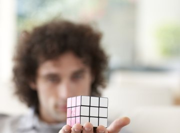 Man holding rubix cube in hand.