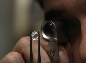 Man looking at diamonds through magnifying glass