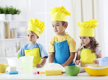 Group of young students dressed in cooking gear in classroom.