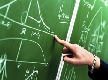 A scientist making calculations on a chalkboard.