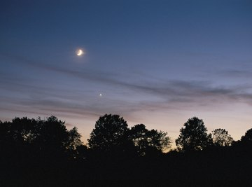 The planet Venus appears just below the moon in the evening sky.