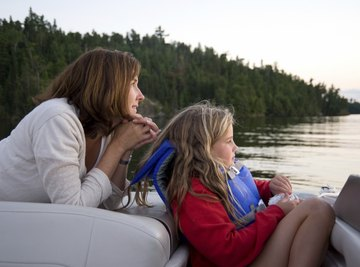 A mother and daughter enjoy a boat ride through the Canadian wilderness.