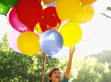 A boy holding balloons filled with helium.