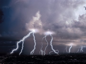 Lighting striking from the clouds at nighttime.