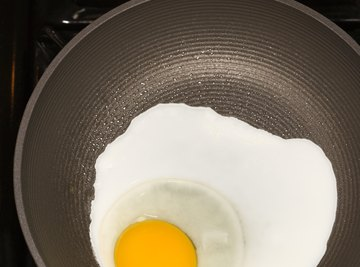 Egg proteins coagulate as they become denatured by heat from a frying pan.